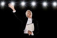 Man in tuxedo holding sheet music