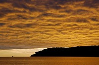 Fishing boat on lake with fire gold clouds at sunrise