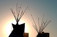 Teepees silhouetted against setting sun