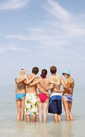 Friends hugging and standing in ocean