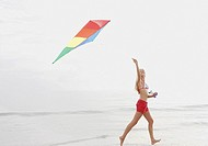 Young woman flying kite on beach