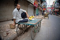 Delhi, India, man selling bananas from cart in market