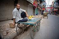 Delhi, India, man selling bananas from cart in market