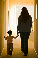 Hispanic mother and daughter walking in hallway