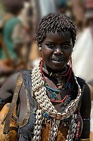Young woman wearing cowry shell necklaces and various adornment market of Keyafer Ethiopia