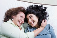 Young woman and mother laughing on bed