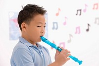 Side profile of a schoolboy playing a flute