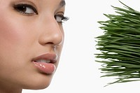 Close_up of a young woman with wheatgrass