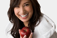 Portrait of a young woman holding an apple and smiling