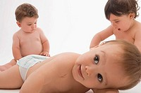 Close_up of two baby boys with a girl