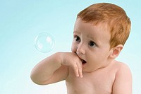 Close_up of a boy looking at a bubble