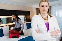 Portrait of a businesswoman standing with her arms crossed with another businesswoman packing her luggage