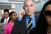Businessman talking on a mobile phone at an airport