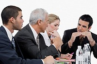Three businessmen and a businesswoman at a meeting in a conference room