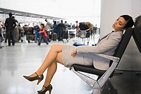 Side profile of a businesswoman sleeping on a chair at an airport (thumbnail)