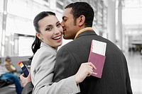 Close_up of a businessman kissing a businesswoman at an airport
