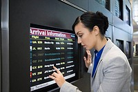 Side profile of a businesswoman looking at an arrival departure board in an airport