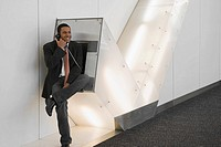 Businessman talking on a pay phone at an airport and smiling
