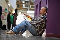 Side profile of a young man holding a textbook and sitting in a corridor (thumbnail)