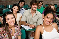 Portrait of university students sitting in a classroom and smiling