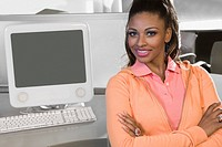 Portrait of a young woman sitting in a computer lab and smiling