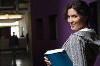 Portrait of a young woman holding a textbook and smiling