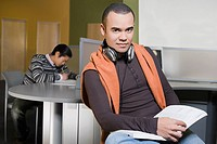 Portrait of a young man holding a book in a computer lab