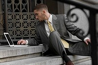 Businessman sitting on steps and using a laptop