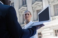 Side profile of a businessman using a laptop with a businesswoman standing in front of him (thumbnail)