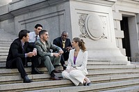 Four businessmen and a businesswoman sitting on steps and discussing