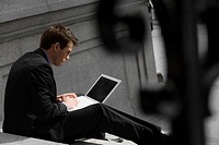 Side profile of a businessman sitting on steps and using a laptop