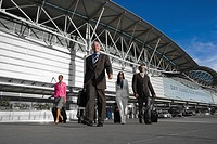 Two businessmen with two businesswomen walking outside at an airport