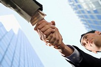 Low angle view of two businessmen shaking hands (thumbnail)