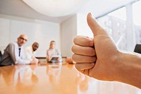 Person's hand showing thumbs up gesture