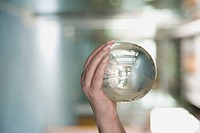 Close_up of a person's hand holding a crystal ball
