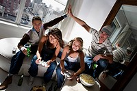 Two young women playing video game and two young men making high five beside them (thumbnail)