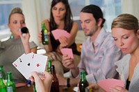 Young man with her friends playing cards (thumbnail)