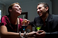 Young couple drinking cocktail and romancing