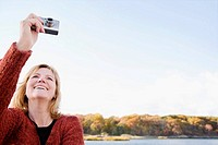 Mature woman photographing with a digital camera and smiling (thumbnail)