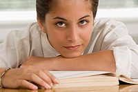Portrait of a teenage girl leaning on a textbook
