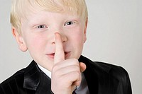 Close_up of a boy with silence gesture