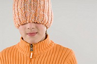 Close_up of a boy hiding his face with a knit hat
