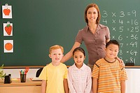 Portrait of a female teacher standing with her three students in a classroom