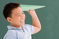 Close_up of a schoolboy playing with a paper airplane