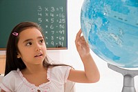 Close_up of a schoolgirl looking at a globe in a classroom