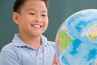 Close_up of a schoolboy looking at a globe in a classroom