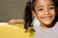 Portrait of a girl in a toy car and smiling (thumbnail)