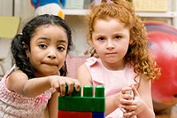 Portrait of two girls playing with plastic blocks