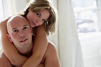 Portrait of a young woman embracing a young man from behind (thumbnail)