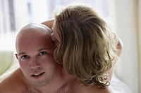 Close_up of a young woman kissing on a young man's head